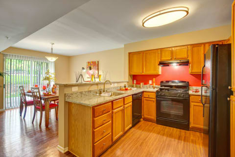 Landover MD Apartments - The Villages at Morgan Metro Kitchen with Wood Floors, Matching Black Appliances, and Dining Room Area