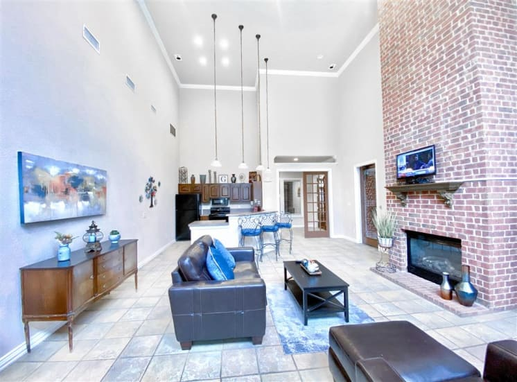 Brick fireplace in community living room at Gates de Provence in North Dallas, TX, For Rent. Now leasing 1, 2 and 3 bedroom apartments.