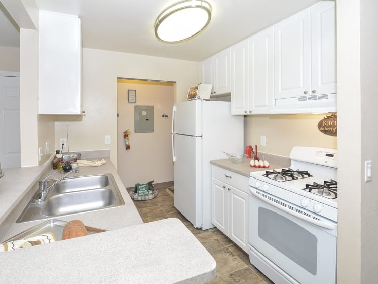 Kitchen with White Cabinetry and Appliances with Light Countertops