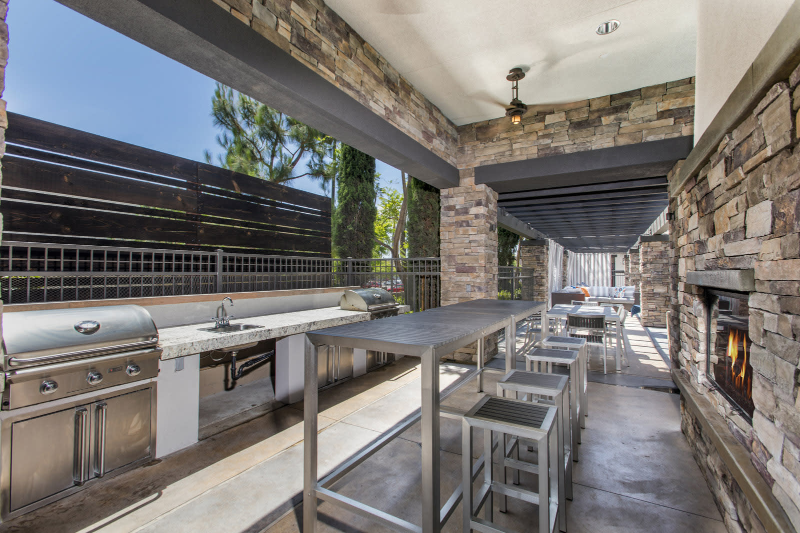 Outdoor grill and seating near fireplace