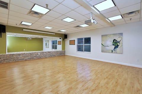 Spacious Yoga Room with Large Mirror and Hardwood Floors