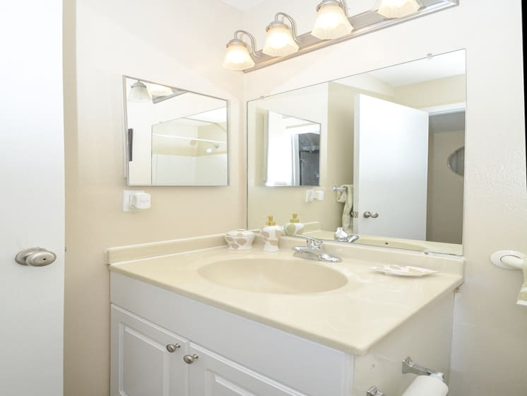 White Bathroom Vanity with Beige Countertop and Large Mirror