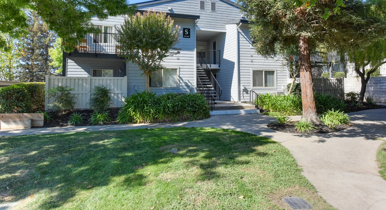 Exterior of Apartment Building with Walk Path, Front Door Entances, Grass, Trees