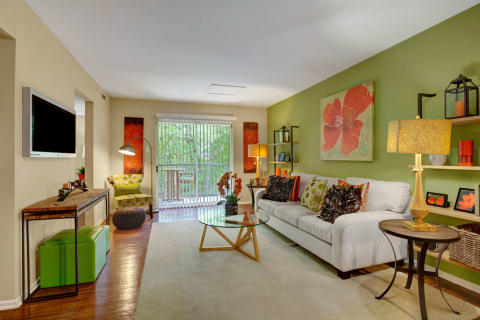 Landover Apartments - Spacious Living Room with Faux-Wood Plank Flooring and Sliding Doors to Patio