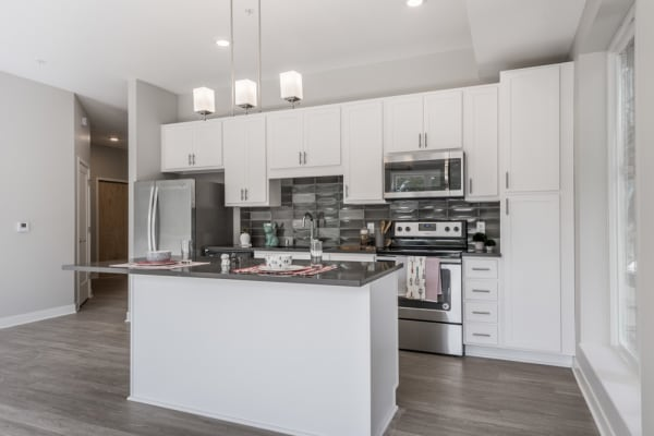 Kitchen with island with white cabinets and dark grey counters