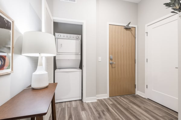 White stacked washer and dryer in closet next to the entry door