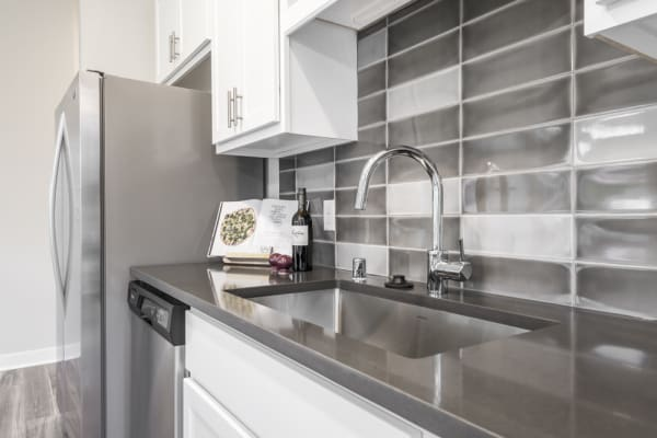 White cabinets in kitchen with dark gray counters and tile backsplash