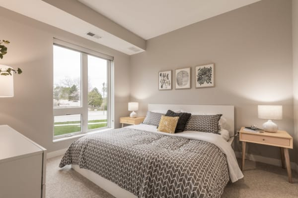 Furnished bedroom with large, floor to ceiling window