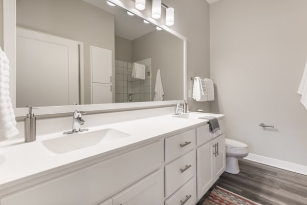 Long bathroom vanity with white cabinets and mirror above