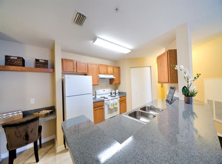 Kitchen with white appliances, breakfast bar, desk area with floating shelves, and tile flooring