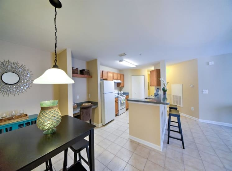 Kitchen with white appliances, breakfast bar, dining room table with pendant lighting, and tile flooring