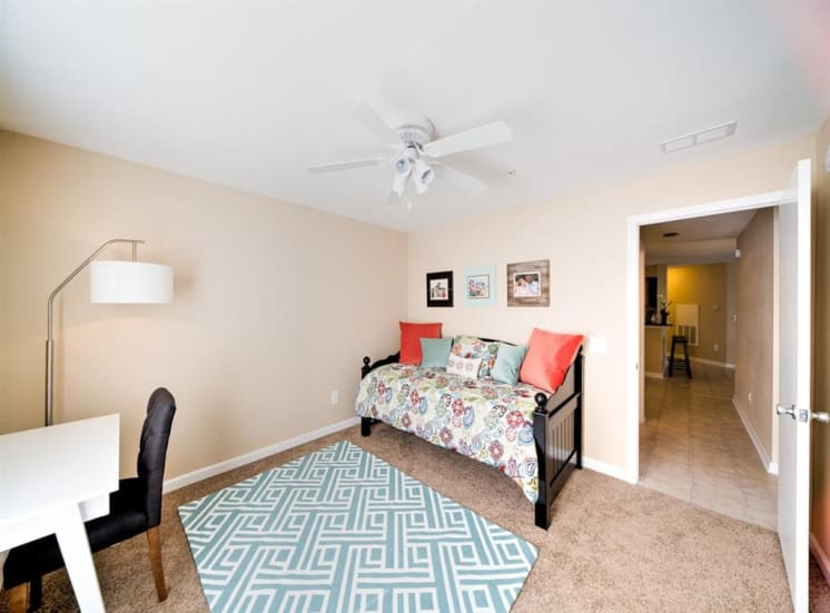 Furnished model bedroom with carpet flooring, rug, multi speed ceiling fan, day bed, desk, chair, floor lamp, and wall art