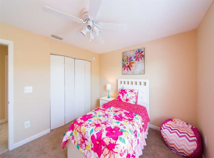 Furnished model bedroom with carpet flooring, multi speed ceiling fan, large closet, and wall art