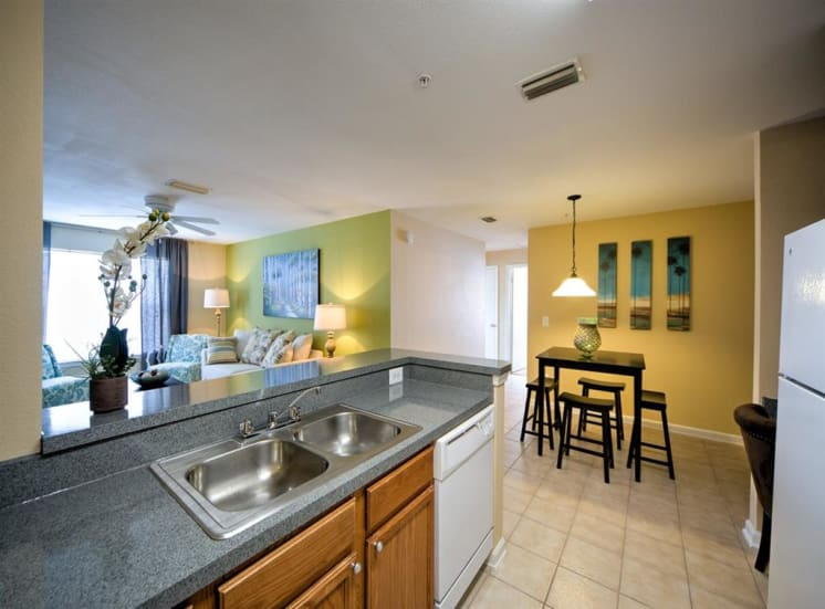 Furnished model kitchen with double basin sink, breakfast bar, overlooking dining room with pendant lighting, and living room
