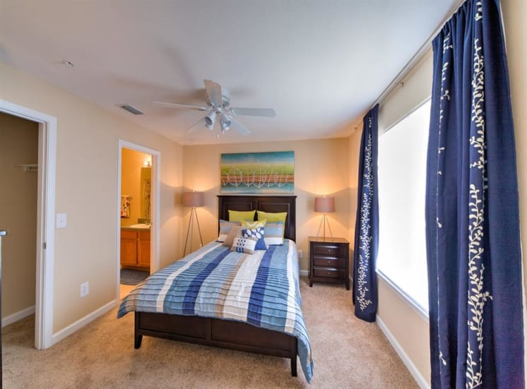 Furnished model bedroom with carpet flooring, day bed, floor lamp, and large window for natural lighting