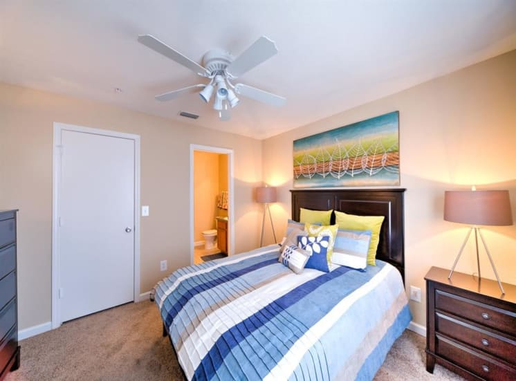 Furnished model bedroom with large closet, in-suite bathroom, carpet flooring, multi speed ceiling fan, side tables, desk lamps, and wall art