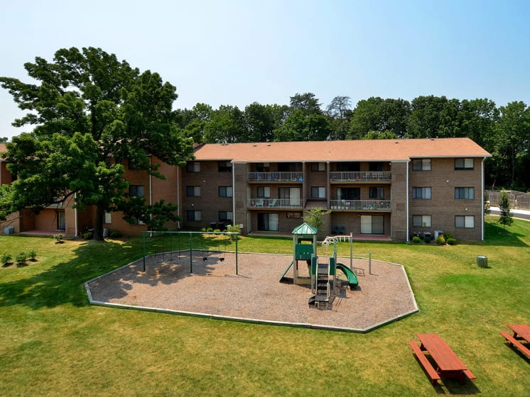 far away view of apartment complex with playground at Gainsborough Court Apartments, Fairfax, VA
