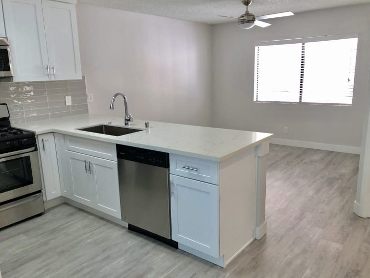Kitchen with Dishwasher, Hardwood Inspired Floors, Sink Countertop, Oven and White Cabinets
