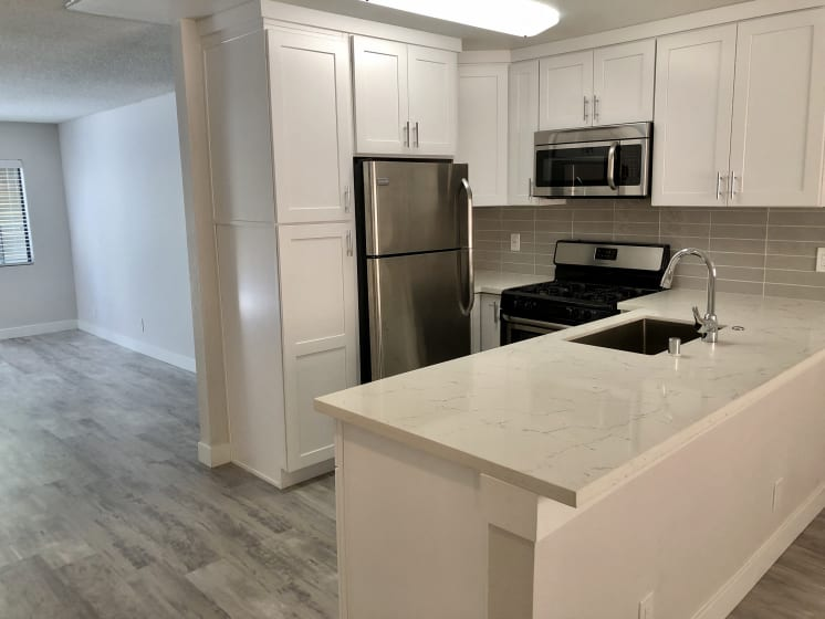 Kitchen with Stove, Hardwood Inspired Floors, Sink Countertop, Oven and White Cabinets