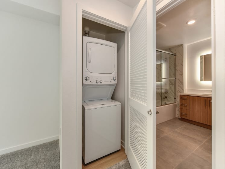 Washer and Dryer in Closet with View of Bathroom Cabinets and Mirror