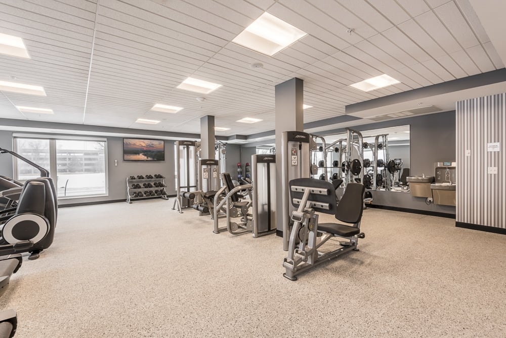 View of expansive gym with weightlifting machines at The Preserve apartments in Bloomington