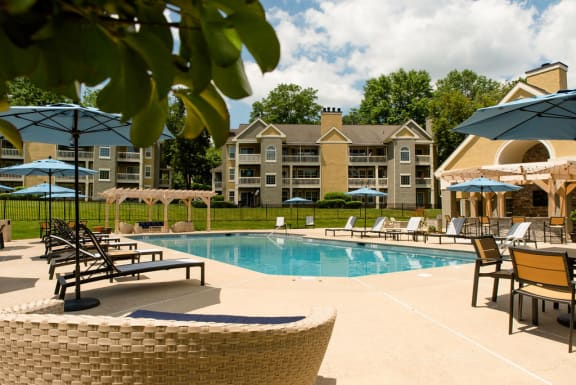 Pool with comfort seting, lounge chairs, and table and chairs with cabana in the back