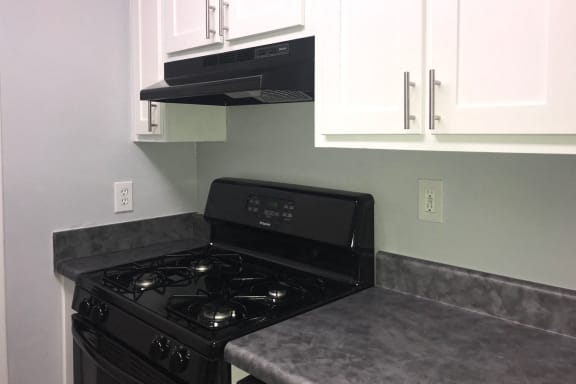 Renovated kitchen showing white cabinets and faux granite countertops