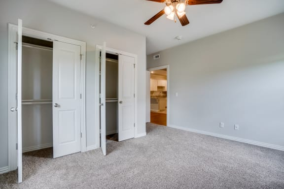 Carpeted Bedroom With Dual Closets & Ceiling Fan