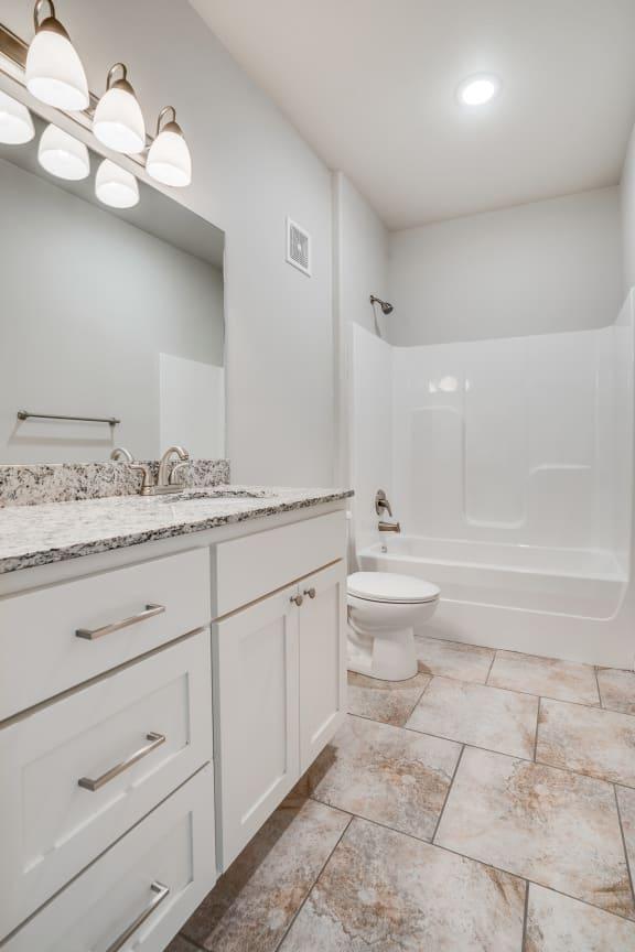 Spacious Bathroom with Granite Countertop Vanity & Tile-Style Flooring