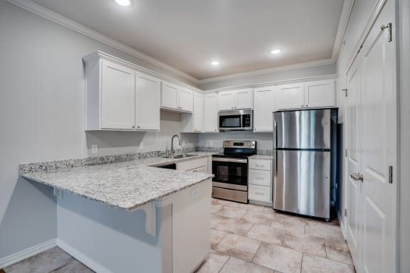 Kitchen With White Cabinets, Granite Countertops & Stainless Steel Appliances