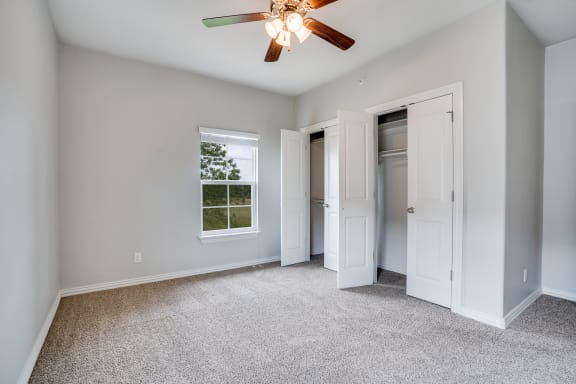 Carpeted Bedroom With Dual Closets