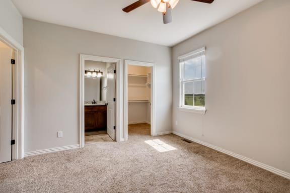 Carpeted Bedroom With Attached Bathroom & Walk-In Closet