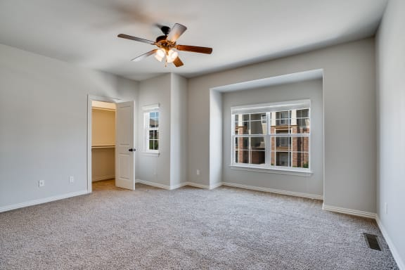 Carpeted Bedroom With Spacious Closet & Ceiling Fan