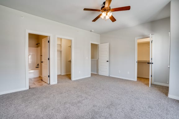 Carpeted Bedroom With Attached Bathroom & Two Walk-In Closets
