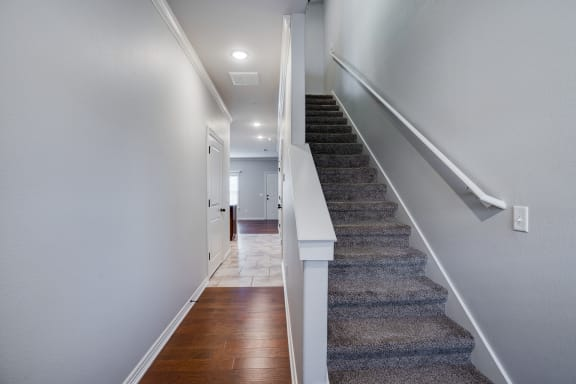 Hallway With Wood-Style Flooring & Carpeted Stairwell Going Upstairs