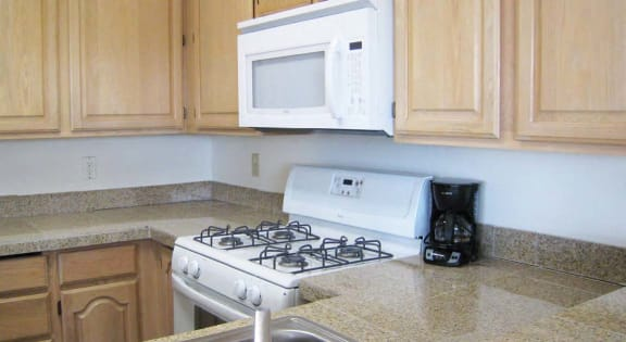Kitchen with upper and lower cabinets, and white microwave and oven with stove cooktop.