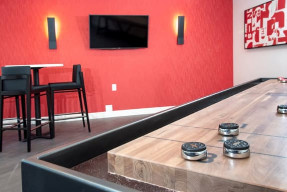 Game Room With Shuffleboard, Red Walls, Seating, and Modern Decor at Eagan Place Apartments