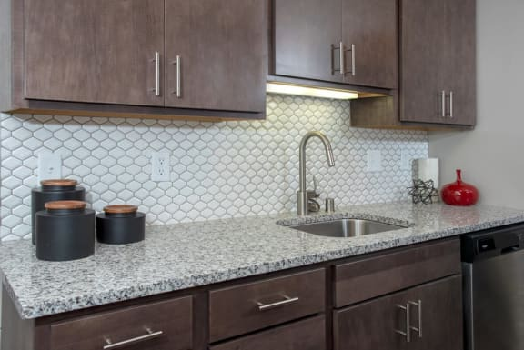Granite Countertops With Modern Backsplash Details in Kitchen at Eagan Place Apartments