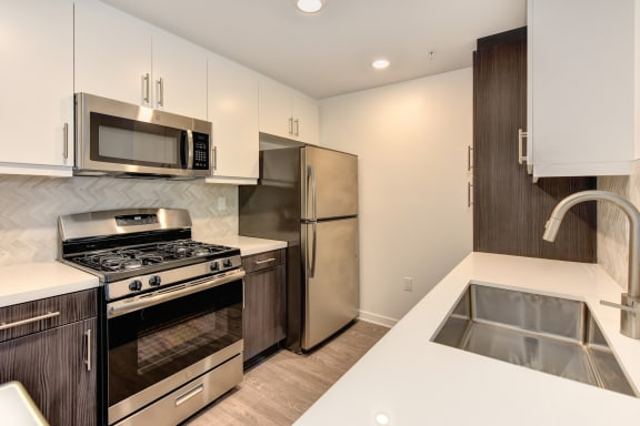 Apartment home kitchen with stainless steel appliances and quartz counters.  There are white upper cabinets and the bottom cabinets are brown