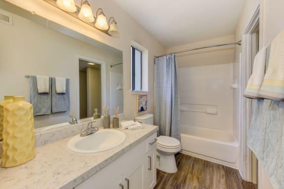 Bathroom with Quartz Counters, Hardwood Inspired Floor, Toilet and Vanity