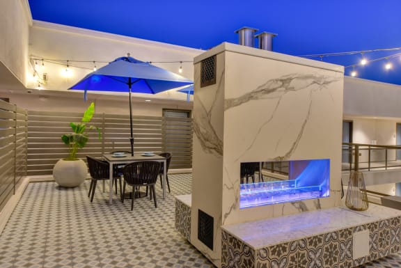 Rooftop lounge area at night.  Fire pit is illuminates and string lights strung above are lit up.  Night blue sky is bright like the blue patio umbrellas at the tables.