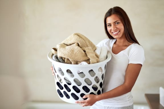 Lady holding laundry basket filled with clean clothes