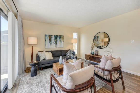 Living room with two tone paint,  Hardwood Inspired Floor, Gray/White Rug, Gray Sofa and Round Mirror