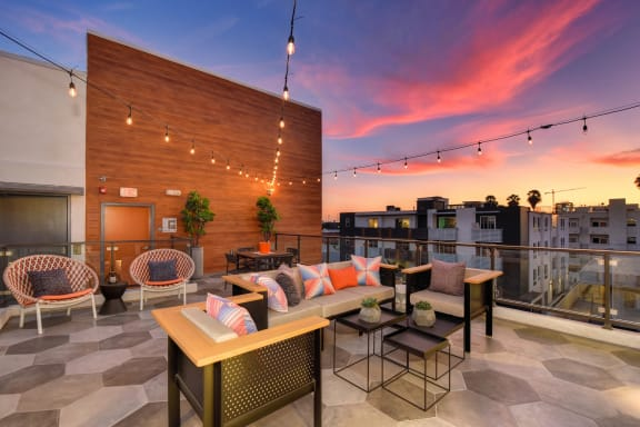 Community rooftop lounge area at dusk with colorful sunset.  Lounge area has table chairs and couches.