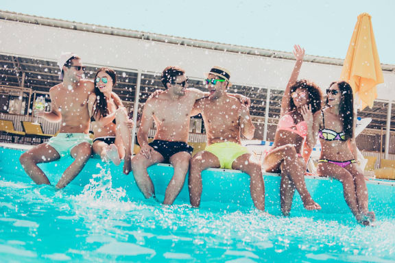 Young teens sitting on the edge of pool while splashing water