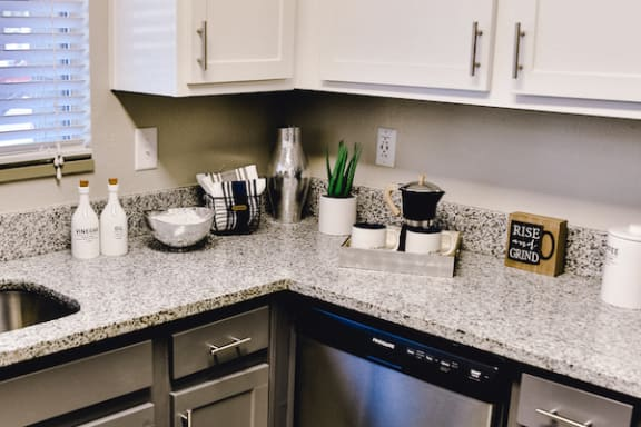 kitchen with granite countertops and white upper cabinetry at The Jameson Apartments, Homewood