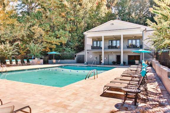 sparkling pool with expansive sundeck, lounge chairs, and clubhouse at The Jameson Apartments, Homewood