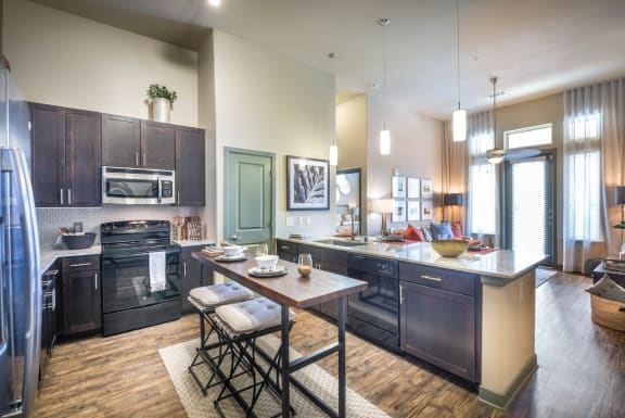 Kitchen with dark wood  cabinets, stainless microwave, refrigerator, a walk-in pantry, and granite countertop. Island with two barstools and decorations and view into living room.