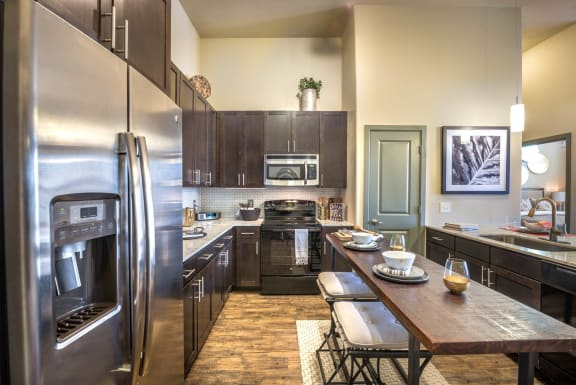 Kitchen with dark wood cabinets, stainless microwave, refrigerator, black stove, a walk-in pantry, and granite countertop. Island with two barstools and decorations and view into bedroom.