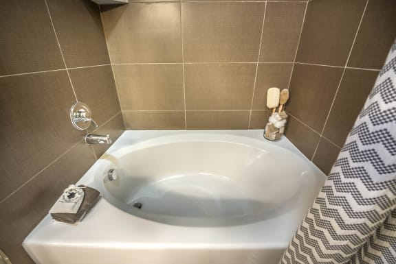 Close up of garden style bath tub and tiled walls